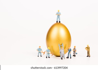 miniature people working with golden egg