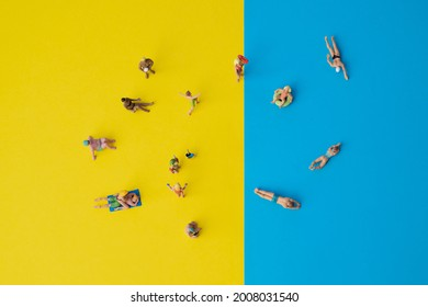 Miniature people: yellow and blue paper as symbol for beach and the sea with swimming or sunbathing people on vacation