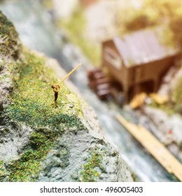 Miniature people: young man playing long trumpet in the mountains. Adventure, travel, tourism, hike and eco nature concept