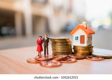 Miniature people,husband and wife standing with mini house and stack coins using as business, family and property concept