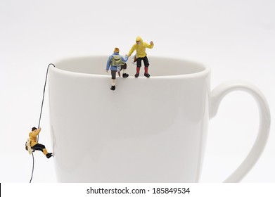 Miniature peoples climb up from coffee cup