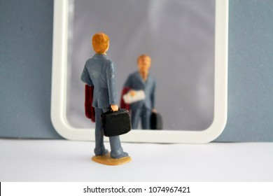 Miniature person man businessman looking to mirror. Business, narcissism, thinking about yourself theme concept.