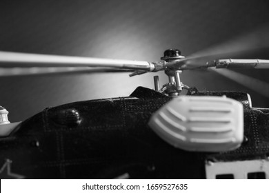 Miniature plastic model of helicopter among dark background scene.