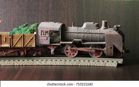 Miniature plastic model of steam locomotive and goods wagon carry tree model also represent christmas event and transportation concept.