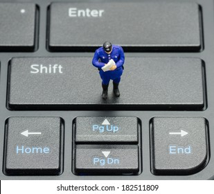 miniature policeman on the keyboard, computer security concept