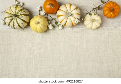 Miniature pumpkins on rustic wood and burlap cloth background. Simple, natural country style fall autumn decorations.
