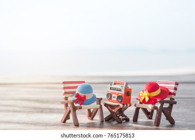 Miniature radio on a table and beach chair with sea background.