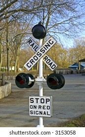 A miniature Railway Crossing sign with lights and bell with 'Stop on Red Signal' sign.  Miniature (park-sized) sign in Centre Island park, Toronto, Ontario, Canada.