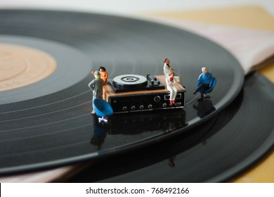 Miniature record player on a background of vinyl. Vintage or retro music listening concept. Listening party or audio entertainment. Appreciation of music, records, audio, songs and MP3's.