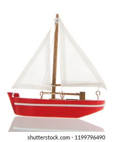 Miniature red sail boat isolated over white background