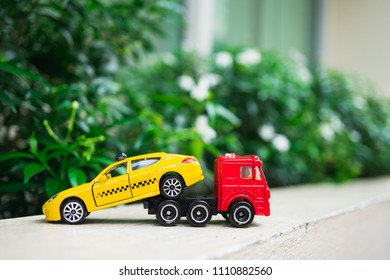 Miniature red trailer lift up broken yellow taxi using as transporation concept