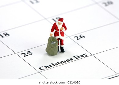Miniature Santa Claus standing on a calendar with Christmas Day printed on it. Christmas concept.