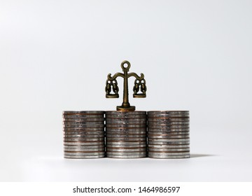 Miniature scales on top of three coin piles.