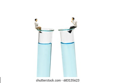 Miniature scientist with a blue chemical tube discussing about chemical composition