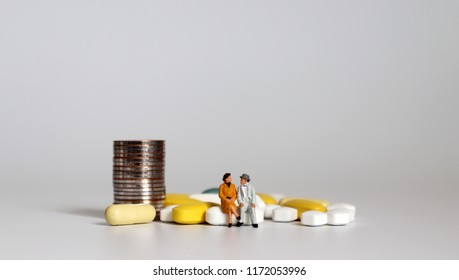 A miniature senior man and a miniature senior woman sitting on a tablet with a pile of coins.
