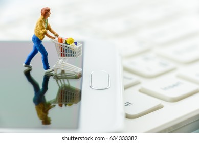Miniature shopper pushes a shopping cart on a white smart phone. Concept of brick and mortar stores nowadays face with increased competition from online ecommerce and decreasing in foot traffic.