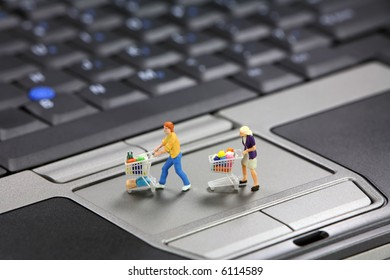 Miniature shoppers with shopping carts on a laptop touch pad mouse. Online shopping concept.
