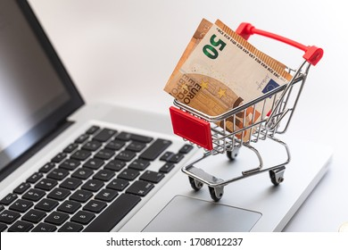Miniature shopping cart with the fifty euro bill inside. Concept of online shopping and e-commerce.