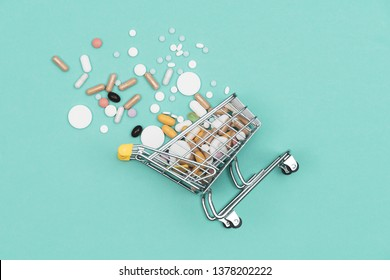 Miniature shopping cart filled with pills, tablets and capsules: pharmacy shopping, medicine and drug abuse concept