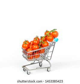 Miniature shopping cart filled with tiny cherry tomatoes isolated on white