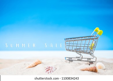 miniature shopping cart on tropical white sand beach over blurred blue sea and clear sky on day noon light.Image for summer vacation shopping  and summer sale concept.