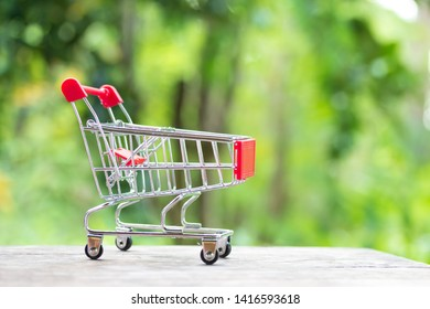 miniature shopping cart on wooden mock up over blurred green garden on day noon light