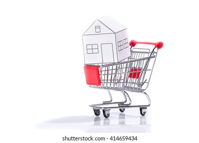 Miniature shopping cart with paper house, isolated on white background