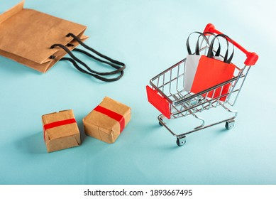 A miniature shopping cart with some bags and some boxes