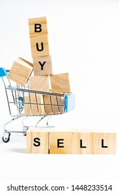 """A miniature shopping trolley with wooden blocks in it, isolated against white background,  with the wordings """"BUY"""" AND """"SELL"""""""