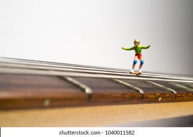 Miniature skateboarding figures grind down guitar strings in macro closeup