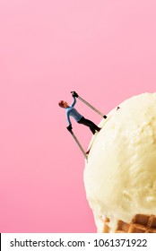 a miniature skier on an ice cream ball, against a pink background with some blank space on top