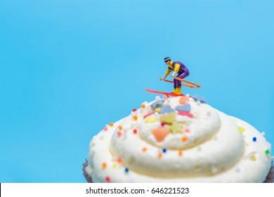 Miniature skier skiing down a cupcake.