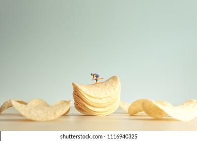 Miniature skier skiing down potatoe chips.