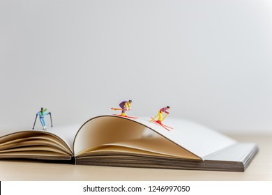 Miniature skiers sliding down the open book. Sport and travel concept.