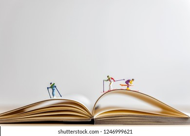Miniature skiers sliding down the open book.