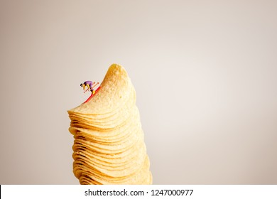 Miniature skiers sliding down the stack of potato chips.