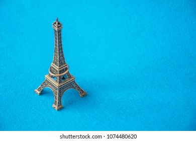 Miniature souvenir statuette of famous French landmark with wedding ring on it. Isolated on blue background and copy space in right side