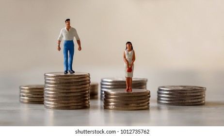 A miniature standing on a pile of coins.