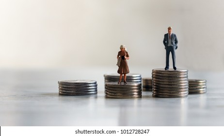 Concept of gender discrimination in pay. A miniature standing on top of a pile of coins.
