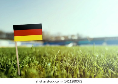 Miniature stick Germany flag on green grass, close up sunny field. Stadium background, copy space for text.