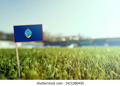 Miniature stick Guam flag on green grass, close up sunny field. Stadium background, copy space for text.