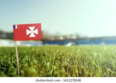 Miniature stick Wallis And Futuna flag on green grass, close up sunny field. Stadium background, copy space for text.