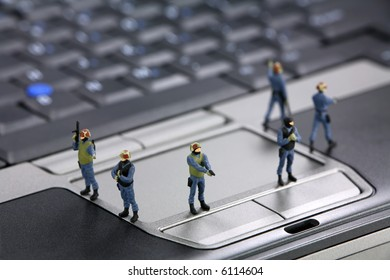 Miniature swat team are guarding a laptop from viruses, spyware and identity thieves. Computer security concept.