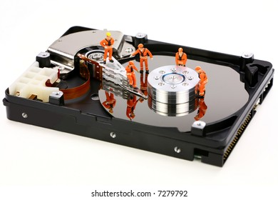 Miniature technicians closely inspecting a hard drive for viruses, spyware and trojans. Computer technician concept.