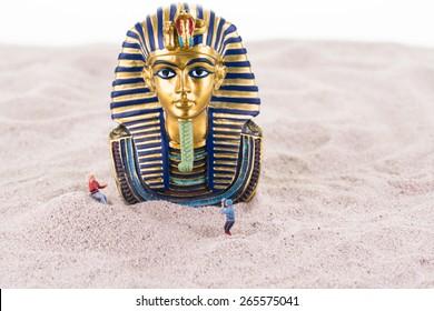 Miniature tourists with the Egyptian King Tutankhamen on sand close up