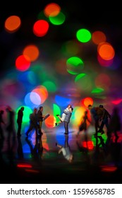 Miniature toy -A couple hugging together among busy commuters crowd with colorful bokeh lights, happiness concept.