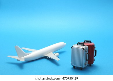 Miniature toy airplane and suitcase on blue background. Trip by airplane.