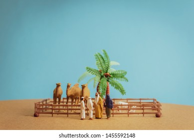 Miniature toy Arab man and wife in abaya buys camel and sheep from a kid on a farm concept.
