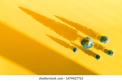 Miniature toy artificial Pine tree on wooden base on bright yellow Christmas background with long shadow. Concept of New Year, Christmas holiday greeting card