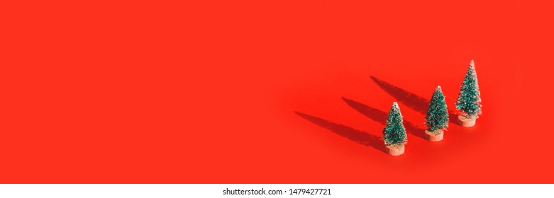 Miniature toy artificial Pine tree on wooden base on bright red Christmas background with long shadow. Concept of New Year, Christmas holiday greeting card
